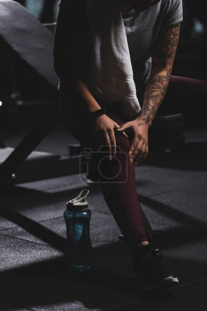 Photo for Cropped view of tattooed african american girl touching knee in gym - Royalty Free Image