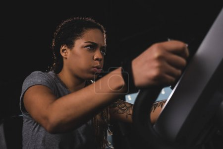 Photo for Selective focus of focused african american girl with smartwatch training on gym machine - Royalty Free Image