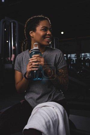 Photo pour Gai et tatoué afro-américaine femme tenant bouteille de sport - image libre de droit