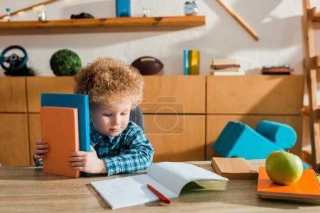 Photo pour Mignon intelligent enfant regardant cahier et tenant des livres - image libre de droit