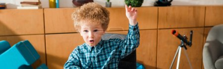 Photo pour Photo panoramique d'un enfant intelligent sur le plan émotionnel avec la main levée à la maison - image libre de droit