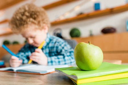 Photo for Selective focus of ripe green apple near smart kid - Royalty Free Image