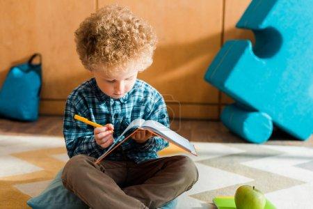 Photo pour Enfant intelligent regardant le cahier et tenant stylo - image libre de droit