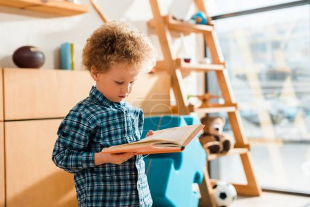 curly and smart child reading book at home