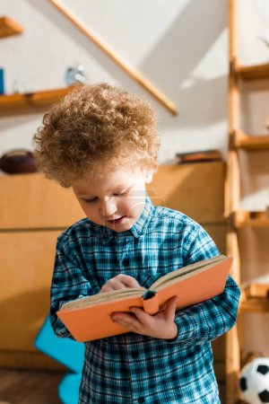 Photo for Smart child smiling while reading book - Royalty Free Image
