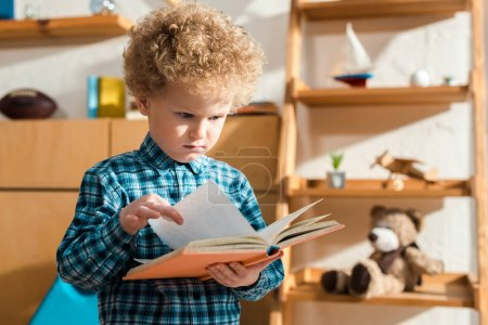 Photo for Displeased and smart child holding book at home - Royalty Free Image