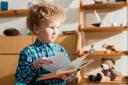 Photo for Curly kid holding book and looking away at home - Royalty Free Image