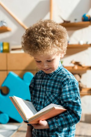 smiling and smart child reading book at home