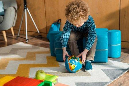 Photo pour Intelligent enfant tenant un globe terrestre près d'une voiture-jouet avec pomme - image libre de droit