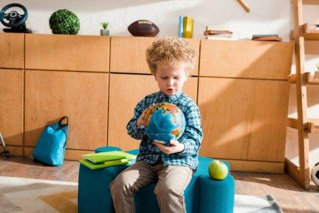Photo pour Enfant intelligent tenant globe tout en étant assis près des livres et de la pomme - image libre de droit