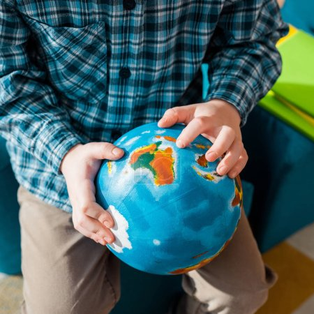 cropped view of smart child holding globe at home