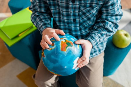 cropped view of smart child holding globe while sitting at home