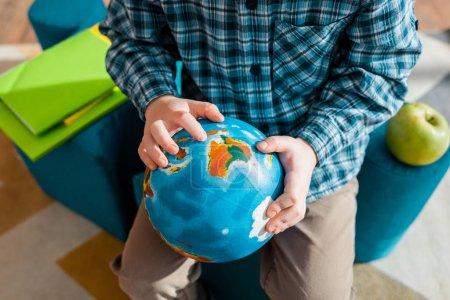 vista recortada de niño inteligente sosteniendo globo mientras está sentado en casa