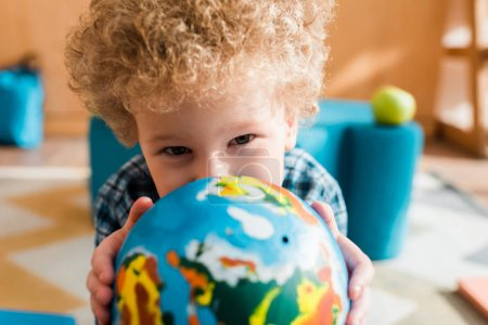 Photo pour Focus sélectif of smart kid holding globe and looking at camera - image libre de droit