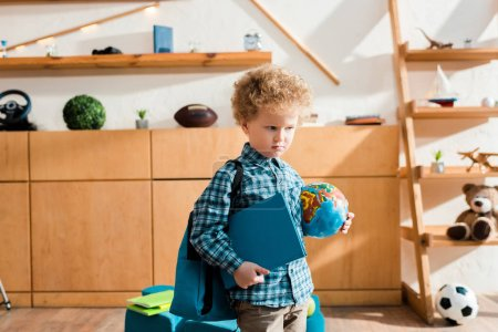 Smart und lockiges Kind mit Rucksack mit Globus und Buch
