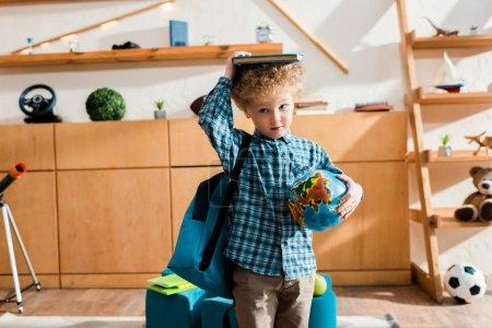 Smart und lockiges Kind mit Rucksack, der Globus und Buch über dem Kopf hält