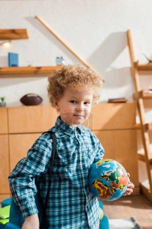 Photo pour Enfant intelligent et bouclé avec sac à dos tenant globe - image libre de droit