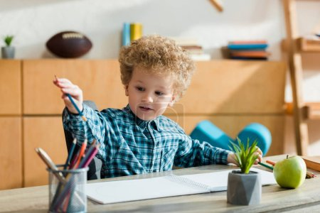 Photo for Selective focus of smart and curly kid taking pencil near ripe apple on table - Royalty Free Image