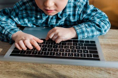 Photo pour Cut view of cute boy tapant sur le clavier de l'ordinateur portable - image libre de droit