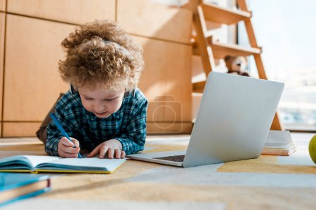 selective focus of kid listening music in wireless headphones while writing near laptop