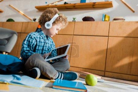 Photo pour Mise au point sélective d'un enfant mignon dans un casque d'écoute utilisant une tablette numérique à écran vierge - image libre de droit