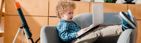 Photo pour Photo panoramique d'un enfant intelligent et frisé à l'aide d'un portable - image libre de droit