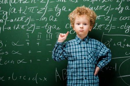 Photo pour Enfant intelligent debout avec la main sur la hanche près du tableau à l'aide de formules mathématiques - image libre de droit