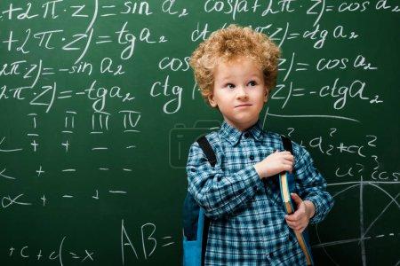 Photo pour Enfant intelligent debout avec un livre près du tableau avec des formules mathématiques - image libre de droit