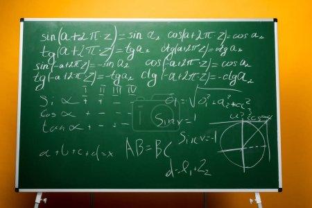 Photo pour Tableau vert avec formules mathématiques sur orange - image libre de droit
