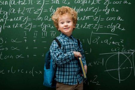 Photo pour Happy child holding book near chalkboard with mathematical formulas - image libre de droit