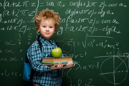 curly kid holding books and fresh apple near chalkboard with mathematical formulas