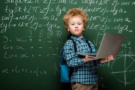 Photo pour Curly kid tenant un ordinateur portable près d'un tableau de craie avec des formules mathématiques - image libre de droit