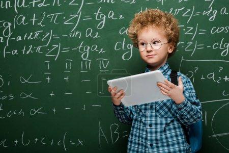 Photo pour Un enfant intelligent dans des verres tenant une tablette numérique près d'un tableau avec des formules mathématiques - image libre de droit
