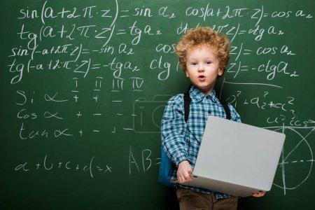 Photo pour Enfant surpris tenant un ordinateur portatif près d'un tableau avec des formules mathématiques - image libre de droit