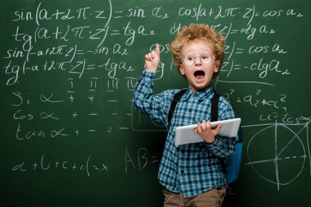 Photo for Smart kid in glasses having idea while holding digital tablet near chalkboard - Royalty Free Image