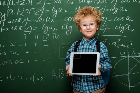 Photo pour Joyeux et intelligent enfant dans des lunettes tenant une tablette numérique avec écran vierge près du tableau avec des formules mathématiques - image libre de droit