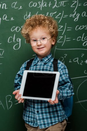 cheerful kid in glasses holding digital tablet with blank screen near chalkboard with mathematical formulas