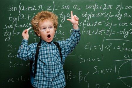 Photo pour Curly kid dans des lunettes en gestation près du tableau à l'aide de formules mathématiques - image libre de droit