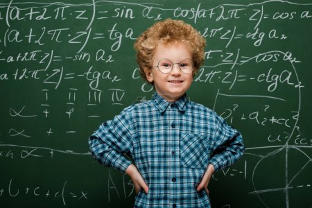 happy kid in glasses standing with hands on hips near chalkboard