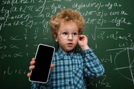 Photo pour Intelligent enfant en lunettes tenant un smartphone avec écran vierge près d'un tableau avec des formules mathématiques - image libre de droit