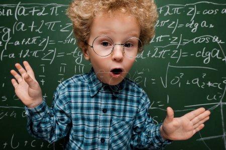 Photo pour Enfant surpris en lunettes regardant la caméra près du tableau à l'aide de formules mathématiques - image libre de droit