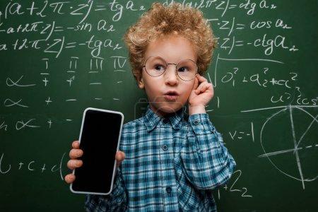 Photo pour Un enfant intelligent tenant un smartphone avec écran vierge et des lunettes près du tableau avec des formules mathématiques - image libre de droit