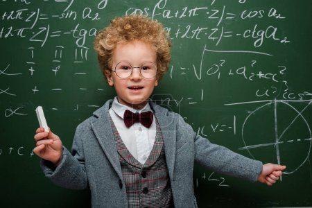 happy kid in suit with bow tie holding chalk near chalkboard with mathematical formulas