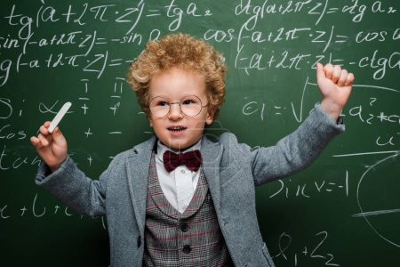 """Photo pour """"smart kid in suit with bow tie holding chalk near chalkboard with mathematical formulas"""" - image libre de droit"""