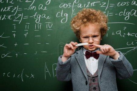 Photo pour Enfant intelligent en costume avec noeud papillon pointant avec le doigt à la craie près du tableau à l'aide de formules mathématiques - image libre de droit