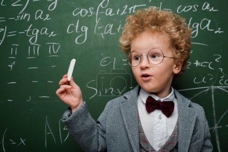 Photo pour Enfant intelligent en costume et noeud papillon tenant la craie près du tableau à l'aide de formules mathématiques - image libre de droit