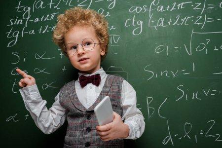 Smart Kind in Anzug und Fliege hält Smartphone in der Hand und zeigt mit dem Finger in die Nähe einer Tafel mit mathematischen Formeln