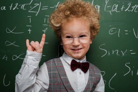 Photo pour Enfant heureux et intelligent en costume et noeud papillon montrant un écriteau près du tableau à l'aide de formules mathématiques - image libre de droit
