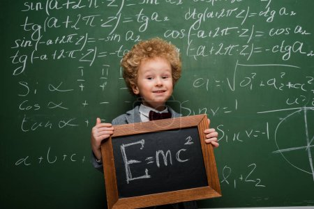 Photo pour Happy kid en costume et noeud papillon tenant un petit tableau avec une formule près du tableau - image libre de droit