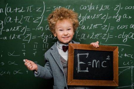 Photo pour Un enfant souriant et intelligent en costume et noeud papillon tenant un petit tableau noir avec une formule près du tableau - image libre de droit